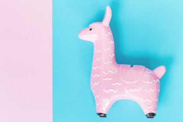 Keuken foto achterwand Lama Pink zine type toy alpaca llama on a blue background close up, coin bank. Creative and fun trendy collage of funky animal concept with copy space
