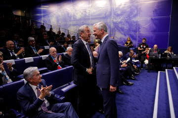"""French Finance Minister Le Maire shakes hands with Governor of the Bank of France Villeroy de Galhau after his speech during a conference entitled """"Bretton Woods: 75 years later"""" in Paris"""