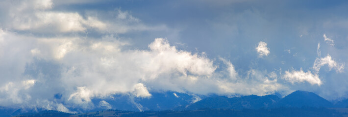 dramatic clouds above the mountain ridge.  panoramic nature background. dynamic side lit cloudscape