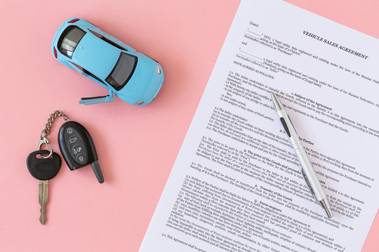 Concept of selling, renting and insuring a car. Flat lay composition. Miniature car model, car keys, sample contract of sale of the car and pen on pink background with copy space ready for mock up.