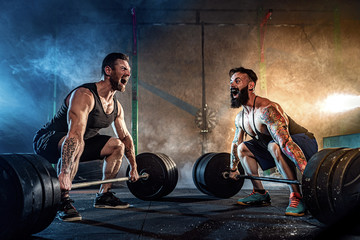 Two muscular bearded tattoed athletes training, lifting heavy weight bar in smoke at gym. Scream. Working hard. Exercise for the muscles of the back Fototapete