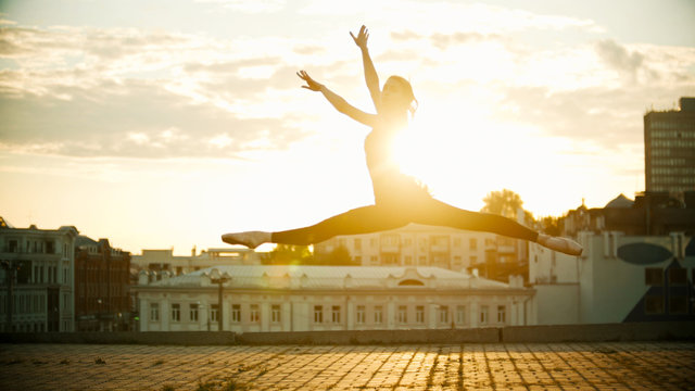 Young woman ballerina jump performing a split on a background of a beautiful bright sunset