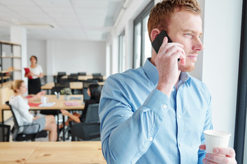 Young businessman in blue shirt talking on mobile phone and looking through the window with business people working in the background at office
