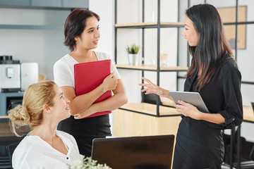 Three young multi-ethnic businesswomen standing and talking to each other during working day at office