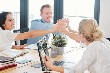 Group of business people sitting at the table together and giving a high five to each other during successful business meeting