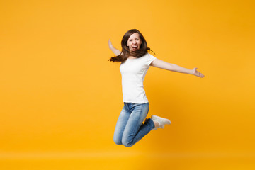 Portrait of funny screaming cheerful young woman in casual clothes jumping, spreading hand wall isolated on bright yellow orange background in studio. People lifestyle concept. Mock up copy space. Wall mural