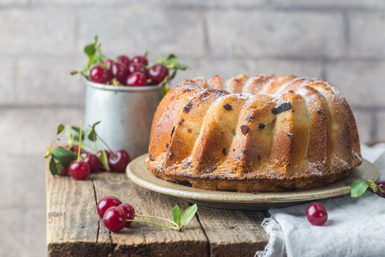Fresh homemade bundt cake with cherry on wooden table