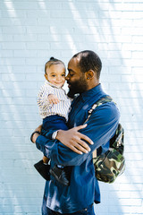 Father carrying his son in front of brick wall