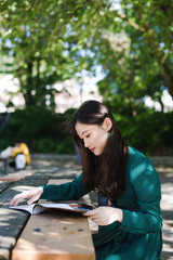 Young woman reading magazine in park