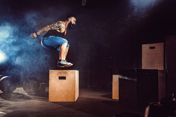 Athlete gave exercise. Jumping on the box. Phase touchdown. Gym shots in the dark tone. Smoke in...
