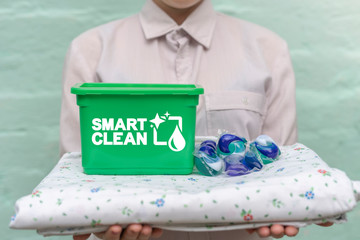 Smart power clean new formula gel laundry pods concept. Textile product and washing capsules on woman's hands. Innovative washing means, modern detergent.