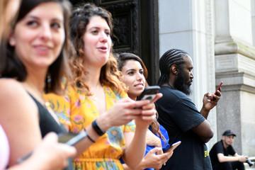 Bystanders wait outside for rapper Meek Mill's departureafter hisretrial hearing in court in Philadelphia