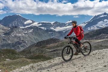 active senior woman, riding her electric mountainbike below the famous Gornergrat in Zermatt, in the background Rimpfischhorn and Strahlhorn,Wallis,Switzerland