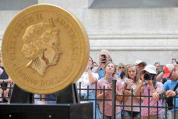 People photograph the world's largest gold bullion coin, the Australian Kangaroo One Tonne Gold Coin, is displayed outside the NYSE in New York