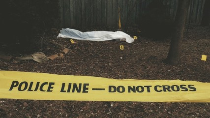 Police tape and a victim of a violent crime under a sheet. With evidence markers.