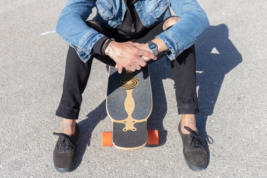 Tattooed young man sitting on longboard, partial view