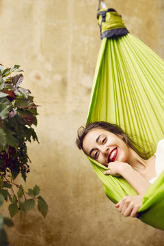 Portrait of smiling young woman relaxing in a hammock on the terrace house. Woman lying and covered with plaid in a hammock. Concept of rest, enjoyment, carefree.