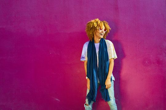 Happy woman standing before a pink wall