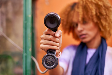Woman holding old-fashioned telephone receiver