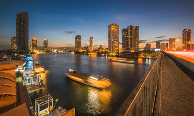 Skyscrapers and Light Trails of Traffic on the Chao Phraya River in Bangkok, Thailand as Seen from Taksin Bridge at Twilight