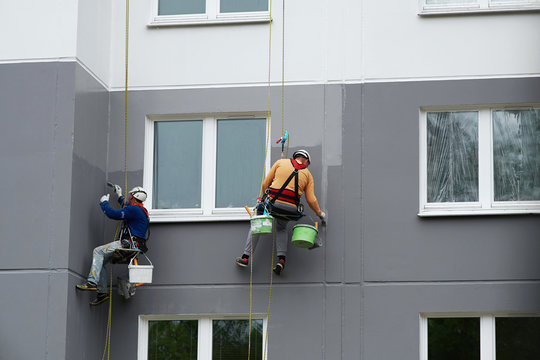 Worker hanging on rope and paints building wall with roller. Painter hanging on cable with paint buckets, industrial climber repairing house facade. Industrial alpinist and climbing. Rigging equipment