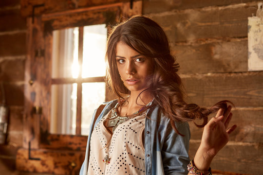 Medium horizontal shot of a beautiful serious young woman in a blue shirt with bracelets and accessories, lifting long brown hair