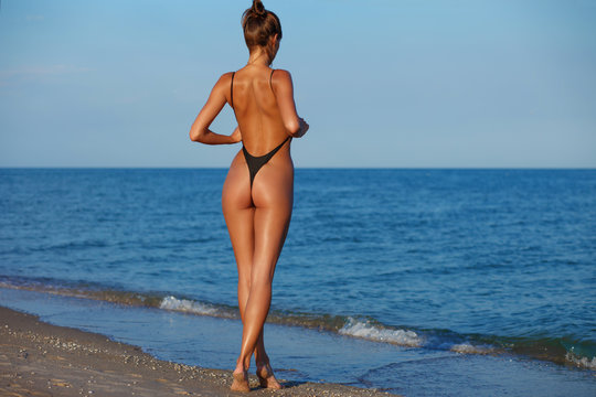 Sexy back of a beautiful woman in black little bikini on sea background. Exotic model at the beach. Sexy buttocks, tanned skin and fit butt