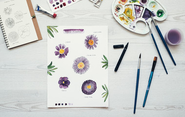 Watercolor painting of purple flowers on the desk, top view