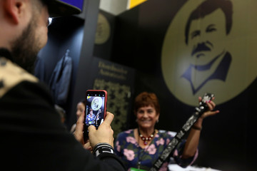 """A woman poses for a photo holding a belt at a stand of the clothing brand """"El Chapo 701"""" at the Intermoda fair in Guadalajara"""