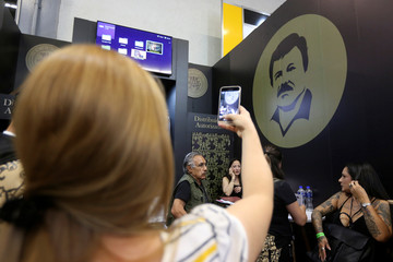 """A woman takes a picture of a stand of the clothing brand """"El Chapo 701"""" at the Intermoda fair in Guadalajara"""