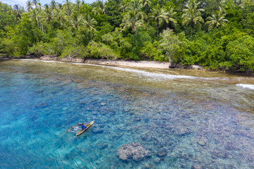 Wall Mural - A villager paddles his outrigger canoe in the warm, blue waters surrounding the island of New Britain in Papua New Guinea. This area is part of the Coral Triangle due to its high marine biodiversity.