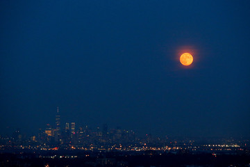 The full moon rises over the skyline of New York and One World Trade Center as seen from West Orange in New Jersey