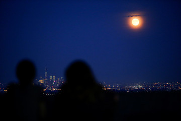 People watch the full moon while it rises over the skyline of New York and One World Trade Center as seen from West Orange in New Jersey