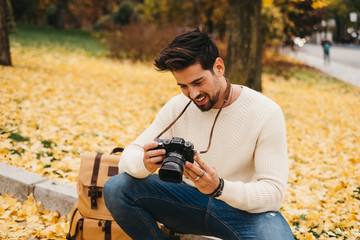 Side view of handsome young photographer in autumn park and watching pictures on camera