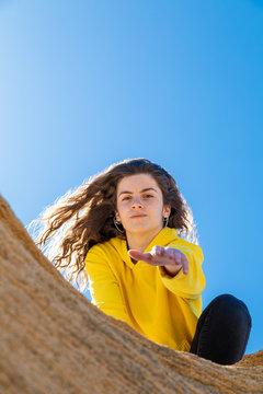 From below brunette woman in yellow sweatshirt giving hand in sandstone rocks on blue sky background