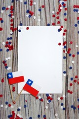 September 18, happy independence day of Chile. memorial day for independence. the concept of patriotism. mini flags and confetti on white wooden background with white paper sheets