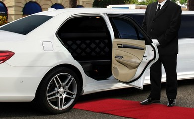 Chauffeur driver standing next to limo opened car door with red carpet