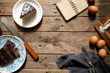From above appetizing cake chocolate eggs napkin and open notebook on wooden table