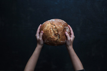 From above tasty appetizing loaf of bread in hands on black background
