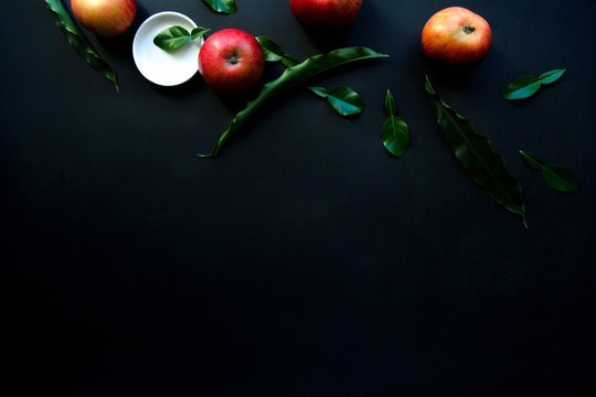 From above bright red appetizing apples with green leaves and white small plate on black background
