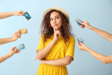 Thoughtful African-American woman and hands with credit cards on color background