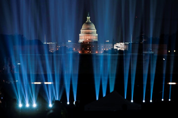 The U.S. Capitol is show behind lights projecting an image of the Saturn V rocket onto the side of the Washington Monument