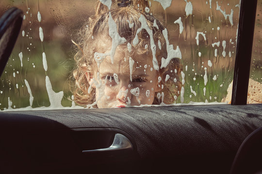 Child washing front glass of car by hand