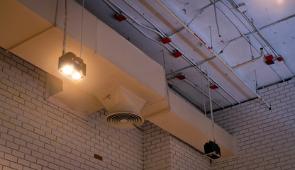 Ceiling lamp with opened light and air duct hanging on ceiling. Air conditioner pipe system. Air ventilation system. Fire sprinkler pipe. Cool system in building. Building interior architecture.