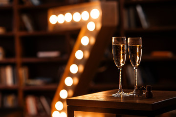 two glasses of champagne in a dark cozy room with a retro lamp