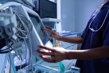 Surgeon using medical equipment in operating room of the hospital