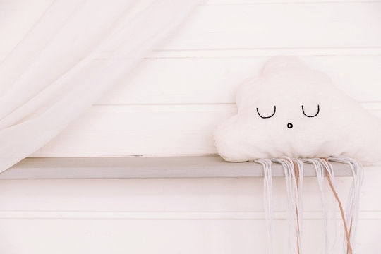 Children's pillow in the shape of a cloud on the background of a wooden wall