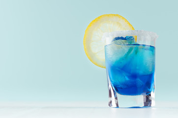 Exotic cold shot glass cocktail with yellow lemon slice, blue curacao, ice cubes, salt rim on soft light mint color background and white wood board. Wall mural
