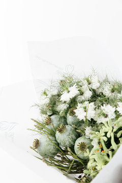 A packed fresh bouquet of flowers, in green and white neutral hues/tones, straight from the flower shop at the market.