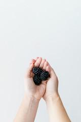 Woman holding fresh blackberries in her hands.
